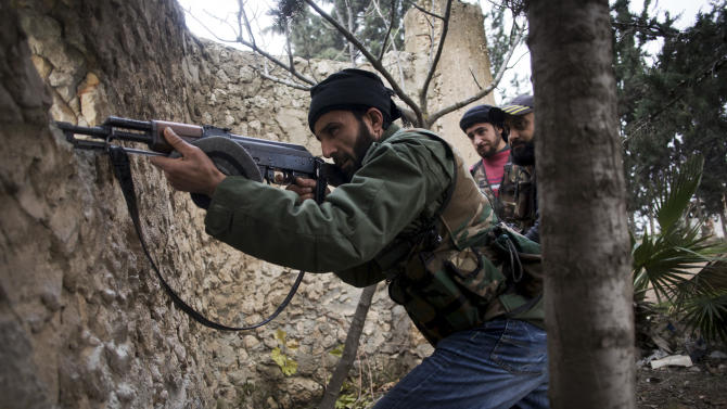 A Free Syrian Army fighter fires at Syrian Army positions in Tal Sheer village, north of Aleppo province, Syria, Thursday, Dec. 13, 2012. (AP Photo / Manu Brabo)