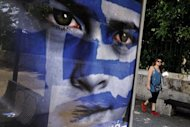 "People walk by an election poster of the Democratic Alliance party in Athens ahead of the May 6 parliamentary elections. The head of Greece's conservatives said Thursday his party aimed to win enough votes in Sunday's election to govern alone with a ""strong mandate"", despite opinion polls suggesting this will be a tall order"