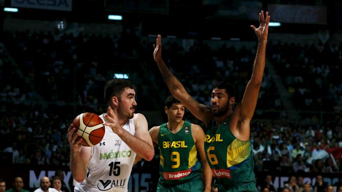 Mexico's Jose Gutierrez controls the ball against Brazil's Augusto Lima and Leonardo Meinfl during their 2015 FIBA Americas Championship basketball game, at the Sport Palace in Mexico City