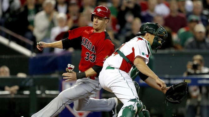 Canada's Justin Morneau (33) scores as Mexico's Humberto Cota waits for the throw during the first inning of a World Baseball Classic game, Saturday, March 9, 2013, in Phoenix. (AP Photo/Matt York)