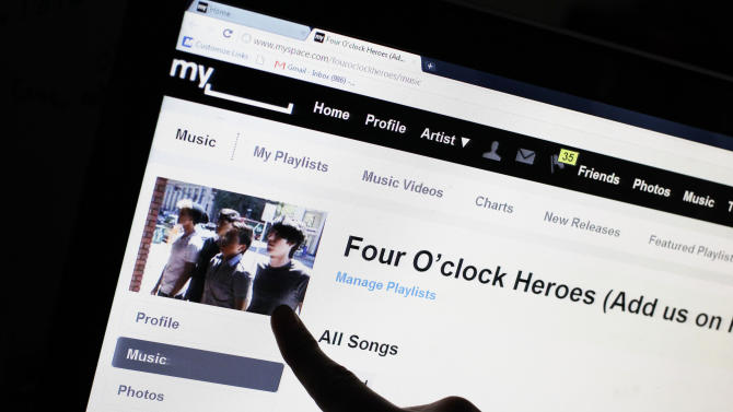 Bass guitarist Cameron Schnittger, with the pop rock band Four O'clock Heroes, points to his picture on on the bands' MySpace web site page in San Jose, Calif., Wednesday, June 29, 2011. News Corp. has sold struggling social networking site MySpace for $35 million, mostly in stock, according to a person familiar with the matter. The deal values MySpace at a fraction of what News Corp. paid for the site six years ago. The sale to online advertising network operator Specific Media is expected to close later Wednesday. (AP Photo/Paul Sakuma)