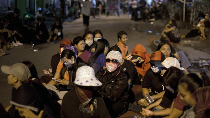Sex workers of Dolly red-light district sit on the road in a protest against the closing of the prostitution complex in Surabaya, East java, Indonesia, Wednesday, June 18, 2014. The government has shut down a red-light district in Indonesia's second largest town amid protests by pimps and sex workers as well as dependents. (AP Photo/Dita Alangkara)
