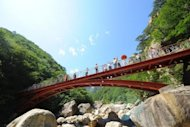 Chinese tourists admiring the view from a bridge at the Mount Kumgang tourist zone in North Korea. South Korea's top official on cross-border affairs says he will consider reopening tours to a North Korean resort despite high tensions