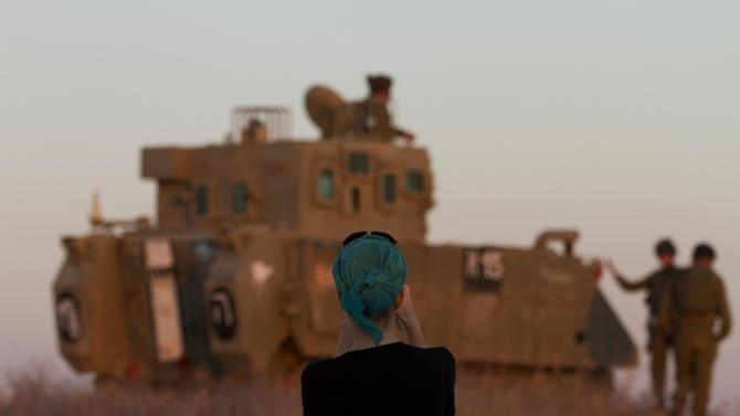 """A woman photographs Israeli soldiers on top an armored personal carrier close to the Israel Gaza Border, southern Israel,Thursday, Nov. 15, 2012. Israel's prime minister says the army is prepared for a """"significant widening"""" of its operation in the Gaza Strip. Benjamin Netanyahu told reporters on Thursday that Israel has """"made it clear"""" it won't tolerate continued rocket fire on its civilians. (AP Photo/Ariel Schalit)"""