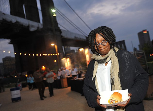FILE - In this Sept. 30, 2012 file photo, Whoopi Goldberg poses with a burger at the New York City Wine and Food Festival&#39;s Burger Bash, in the Brooklyn borough of New York. Goldberg teams up in October 2012 with celebrity chef, Art Smith, with help on tunes from Questlove, to serve up a couple dozen inspired takes on one of America&#39;s favorite fried foods, chicken. The event is part of the fifth annual New York City Wine and Food Festival. (AP Photo/Diane Bondareff, File)
