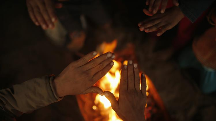 Members of a Palestinian family warm themselves by fire on rainy day in northern Gaza Strip