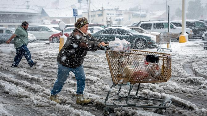 Brenda Nolting, of Rapid City, S.D., rolls her cart to her car after stocking up on necessities Friday, Oct. 4, 2013 at a local supermarket in Rapid City. An early snow storm has swept through Wyoming and western South Dakota, dropping more than a foot of snow in places. (AP Photo/Steve McEnroe)