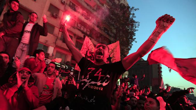 An Egyptian protester waves a flare during a rally of thousands of soccer fans of Egypt's most popular team, Al-Ahly, in Tahrir Square, the focal point of Egyptian uprising, in Cairo, Egypt, Friday, Jan. 18, 2013. Fans called for revenge a week before a court verdict is expected over last year's Port Said football stadium disaster, which killed 72 fans. (AP Photo/Khalil Hamra)