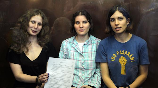 FILE - In this Friday, Aug. 17, 2012 file photo, feminist punk group Pussy Riot members, from left, Maria Alekhina, Yekaterina Samutsevich, and Nadezhda Tolokonnikova show the court's verdict as they sit in a glass cage at a courtroom in Moscow. The two-year prison sentence handed down to Pussy Riot for a provocative protest inside a Moscow cathedral called attention to just how hard President Vladimir Putin is clamping down on minor displays of dissent. But Russia isn't the only country where people are punished for offenses that many in the West might consider trivial. (AP Photo/Mikhail Metzel, File)