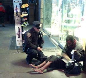 """This photo provided by Jennifer Foster shows New York City Police Officer Larry DePrimo presenting a barefoot homeless man in New York's Time Square with boots Nov. 14, 2012 . Foster was visiting New York with her boyfriend on Nov. 14, when she came across the shoeless man asking for change in Times Square. As she was about to approach him, she said the officer  came up to the man with a pair of all-weather boots and thermal socks on the frigid night. She took the picture on her cellphone. It was posted Tuesday night to the NYPD's official Facebook page and became an instant hit. More than 350,000 users """"liked"""" it as of Thursday afternoon, and over 100,000 shared it. (AP Photo/Jennifer Foster)"""