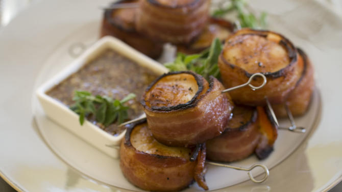 This Nov 4, 2013 photo shows grilled bacon wrapped scallops in Concord, N.H. This all-protein finger food appetizer is perfect for holiday entertaining. (AP Photo/Matthew Mead)