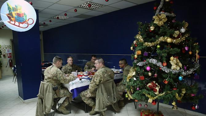 NATO service members enjoy their meal during Christmas celebrations at ISAF headquarter in Kabul, Afghanistan on Thursday, Dec. 25, 2014. U.S. senator John McCain is in Kabul for Christmas day. The former presidential candidate met with Afghan president Ashraf Ghani and his chief executive officer Abdullah Abdullah in separate meetings during his visit on Thursday. (AP Photo/Massoud Hossaini)