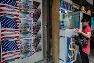 A woman looks into her wallet at a currency exchange booth in Hong Kong on October 22, 2012. Hong Kong&#39;s de facto central bank said Wednesday it expects more capital inflows into the city after its fourth intervention in the forex market in a week to curb the local dollar&#39;s strength