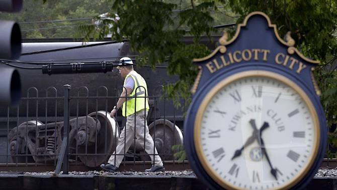 An official walks past part of a CSX freight trail that derailed overnight in Ellicott City, Md., Tuesday, Aug. 21, 2012. Authorities said two people not employed by the railroad were killed in the incident. (AP Photo/Patrick Semansky)