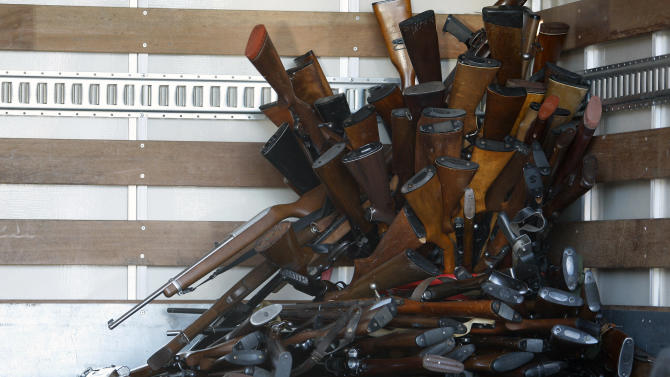 Guns that were turned in by their owners are seen in a trash bin at a gun buyback held by the LAPD