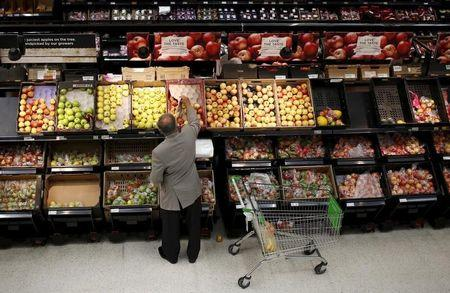 A man chooses apples in an Asda store in northwest London
