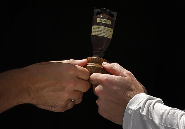 Australia's cricket team captain Clarke holds a replica Ashes urn with England's team captain Cook in Brisbane