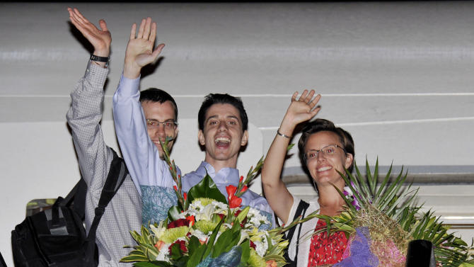 """Freed Americans Shane Bauer, left, Josh Fattal, center, and Sarah Shourd, right, Bauer's fiance, wave from the door to an airplane before leaving for the United States at the airport in Muscat, Oman, Saturday, Sept. 24, 2011. Two Americans freed from an Iranian prison told reporters Saturday they were """"eager to go home"""" just before boarding their flight to the U.S. from Oman, the Gulf state that helped mediate their release after more than two years in custody on accusations of spying. Josh Fattal and Shane Bauer were scheduled to arrive home on Sunday, according to Samantha Topping, a spokeswoman for their families. The two were released from Tehran's Evin prison under a $1 million bail deal and arrived in Oman on Wednesday in the first leg of their journey home. There they were reunited with joyful relatives. (AP Photo/Sultan al-Hasani)"""