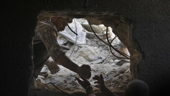 Syrians look for the bodies two girls thought to be under the rubble of a building hit by a Syrian government airstrike in Aleppo, Syria, Sunday, Aug. 19, 2012 (AP Photo/ Khalil Hamra)
