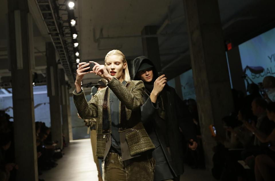 Models walk the runway snapping photos on their cell phones during the presentation of the Kenneth Cole Fall 2013 fashion collection during Fashion Week in New York, Thursday, Feb. 7, 2013.  (AP Photo/Kathy Willens)