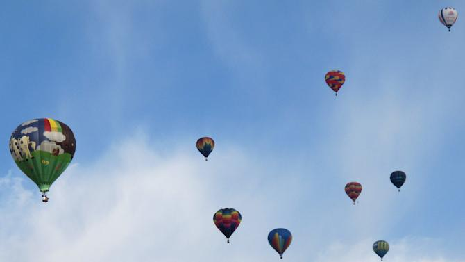 Hot air balloons float over Albuquerque, N.M., on the third day of the Albuquerque International Balloon Fiesta Monday, Oct. 4, 2010. (AP Photo/Tim Korte)