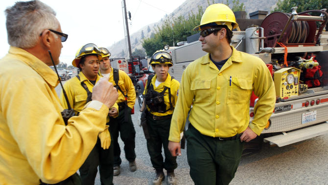 Firefighters get instructions as they ready to head toward a wildfire near the end of Number 1 Canyon Road Monday, Sept. 10, 2012, near Wenatchee, Wash. Crews in central Washington and Wyoming worked Monday to protect homes from two of the many wildfires burning throughout the West as a destructive fire season stretches into September with no relief expected from the weather anytime soon. The National Weather service issued red-flag warnings for wide swaths of eastern Washington and Oregon, Idaho, Montana and all of Wyoming, meaning conditions could exacerbate blazes. (AP Photo/Elaine Thompson)