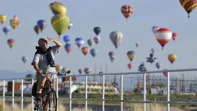An unidentified bicyclist watches the mass ascension of hot air balloons while on a early morning bike ride along the North Diversion Channel path during the first morning of the Albuquerque International Balloon Fiesta, Saturday, Oct. 2, 2010, in Albuquerque, N.M. (AP Photo/Albuquerque Journal, Marla Brose) **EXAMINER ONLINE OUT**