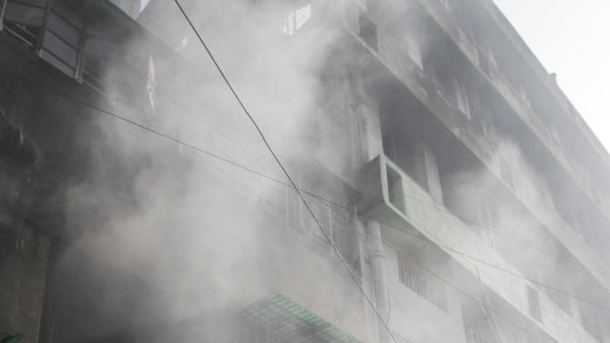Firemen wait outside as smoke arises after a fire broke out early morning at an illegal six-story plastics market in Kolkata, India, Wednesday, Feb.27, 2013. More than a dozen people were killed and others were hospitalized in critical condition. (AP Photo/Bikas Das)