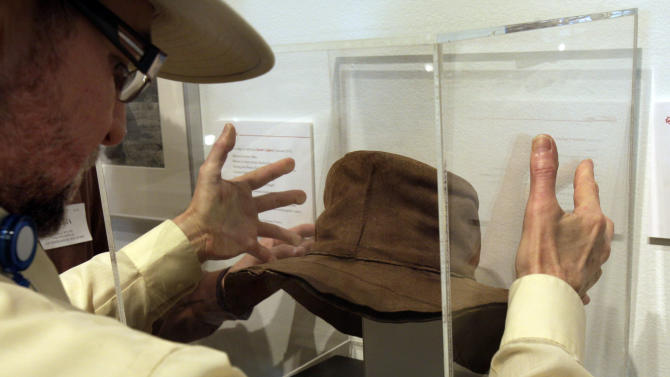 """Museum Installer Rene Ronda places a protective plexiglass cube cover over a hat by designer by Edith Head, from the 1975 movie """"Rooster Cogburn,"""" as part of the """"Katharine Hepburn: Dressed for Stage and Screen"""" exhibit in the New York Public Library for the Performing Arts at Lincoln Center,  Tuesday, Oct. 16, 2012. (AP Photo/Richard Drew)"""