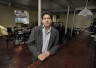 FILE - In this file photo of Dec. 4, 2012, photo, proprietor Adam Weprin, of the Bridge Cafe, in New York&#39;s South Street Seaport, poses for a photo at the restaurant&#39;s bar after his establishment was shuttered by Superstorm Sandy. Nearly four months after Superstomr Sandy hit, the historic cobblestone streets near the water&#39;s edge in lower Manhattan are eerily deserted, and among local business owners, there is a pervasive sense that their plight has been ignored by the rest of Manhattan. (AP Photo/Richard Drew, File)