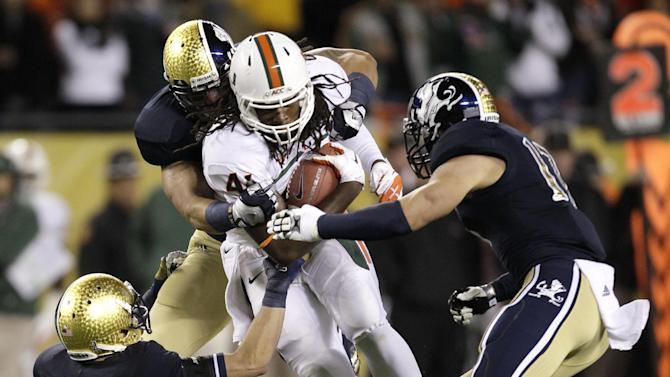Miami tight end Clive Walford, center, advances the ball and is tackled by Notre Dame cornerback Bennett Jackson (2), Manti Te'o, behind, and Zeke Motta (17), during the first half of an NCAA college football game at Soldier Field Saturday, Oct. 6, 2012, in Chicago. (AP Photo/Nam Y. Huh)
