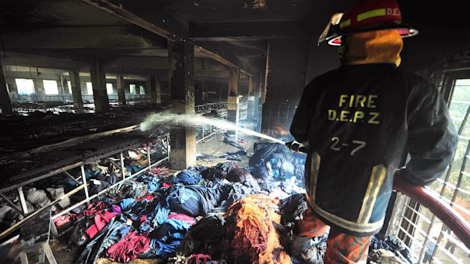 A firefighter douses the inside of a garment factory outside Dhaka, Bangladesh, Sunday, Nov. 25, 2012. At least 112 people were killed in a late Saturday night fire that raced through the multi-story garment factory just outside of Bangladesh's capital, an official said Sunday. (AP Photo/ khurshed Rinku)