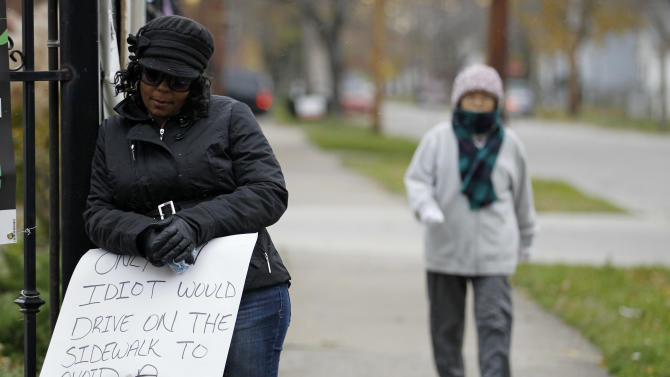 A woman walks by as Shena Hardin, left,  holds up a sign  to serve a highly public sentence Tuesday, Nov. 13, 2012, in Cleveland. Hardin was caught on camera driving on a sidewalk to avoid a Cleveland school bus that was unloading children.  A Cleveland Municipal Court judge ordered 32-year-old Hardin to serve the highly public sentence for one hour Tuesday and Wednesday.(AP Photo/Tony Dejak)