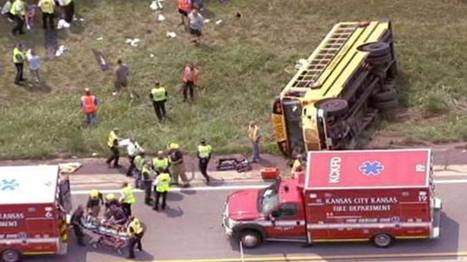 This image from video provided by KMBC-TV shows the scene of a school bus crash Wednesday, Aug. 21, 2013, in Bonner Springs, Kan. A spokeswoman for a private Kansas City, Mo., school says eight sixth-grade girls have sustained noncritical injuries after their school bus overturned in Bonner Springs, Kan. The spokesperson says the bus was carrying 30 girls to a campout. (AP Photo/Courtesy KMBC-TV)