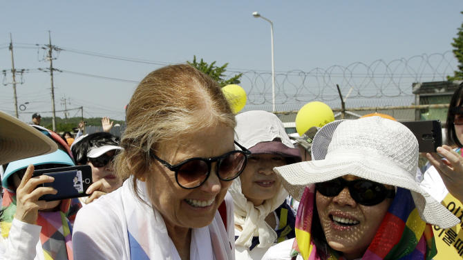 U.S. activist Gloria Steinem, left, is greeted by South Korean activists after they crossed the Unification bridge by bus near the border village of Panmunjom, in Paju, north of Seoul, South Korea, Sunday, May 24, 2015. International women activists including Gloria Steinem and two Nobel Peace laureates on Sunday were denied an attempt to walk across the Demilitarized Zone dividing North and South Korea, but were allowed to cross by bus and complete what one of them called a landmark peace event. (AP Photo/Lee Jin-man)