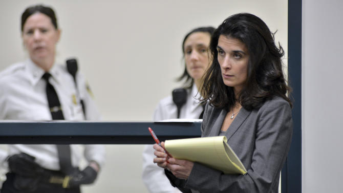 Defense Attorney Melinda Thompson listens to the judge while court officers, rear, stand beside Aisling McCarthy Brady, who remained hidden during a hearing at Cambridge, Mass., District Court Friday, Feb. 22, 2013.  Lawyers for Brady, a nanny charged with assault and battery of a one-year-old girl in Cambridge, won a request during the hearing to preserve evidence in the case.  Brady arrived from Ireland in 2002 on a tourist visa. (AP Photo/The Boston Globe, Josh Reynolds, Pool)