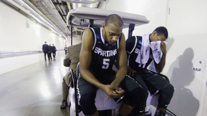 Michigan State forward Adreian Payne (5) and guard Keith Appling leave on a cart after a regional semifinal against Duke in the NCAA college basketball tournament, Saturday, March 30, 2013, in Indianapolis. Duke won 71-61. (AP Photo/Darron Cummings)