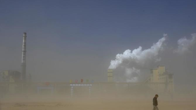 File photo of a man walking past a coal plant amidst a dust storm in Lingwu, Ningxia Hui Autonomous Region