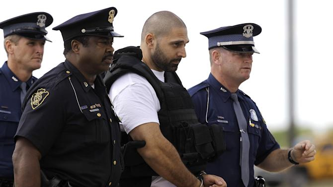 FILE - In this Aug. 26, 2010 file photo, Elias Abuelazam is escorted by authorities after arriving on a flight in Flint, Mich. Abuelazam, serving a life sentence for murder in a series of stabbings in the Flint area is suing to be deported to Israel, his home country. Elias Abuelazam says he committed attempted murder there in 2009 and is willing to stand trial and be sent to prison. His lawsuit against the federal government has been transferred to Washington from a federal court in Grand Rapids. (AP Photo/Paul Sancya)