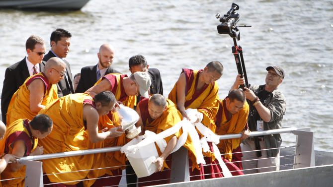 The Dalai Lama, center left in baseball cap, pours mandala sand mixed with river water into the Anacostia River as part of a blessing ceremony Saturday, July 16, 2011, in Washington. President Barack Obama held a White House meeting Saturday with the Dalai Lama, a fellow Nobel Peace Prize laureate, hours after China called on the U.S. to rescind an invitation that could sour relations with Beijing. (AP Photo/Jacquelyn Martin)