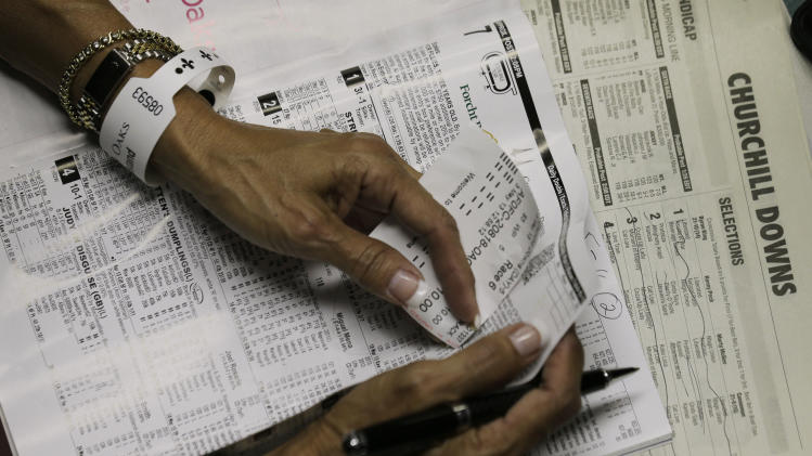 A spectator checks her betting tickets after the seventh race before the running of the 139th Kentucky Oaks at Churchill Downs Friday, May 3, 2013, in Louisville, Ky. (AP Photo/Charlie Riedel)