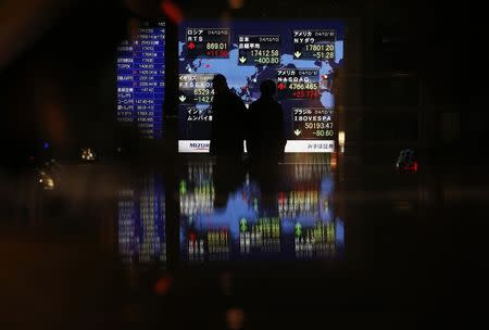 Passersby are silhouetted in front of an electronic board displaying Japan's Nikkei average and various countries' stock price index outside a brokerage in Tokyo
