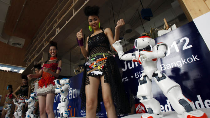 """Models dance with the humanoid robot """"NAO"""" during a news conference in Bangkok"""