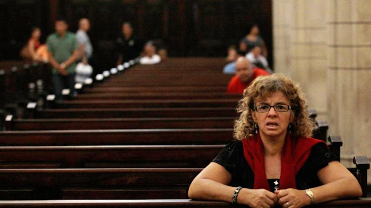 A woman recites the rosary at a local Catholic church where supporters of the ailing President Hugo Chavez gathered to pray for his health, in Caracas,Venezuela, Thursday, Dec. 13, 2012.  Venezuelans were warned that Chavez may not be well enough after his fourth cancer-related surgery in Cuba to be inaugurated on Jan. 10.  (AP Photo/Fernando Llano)