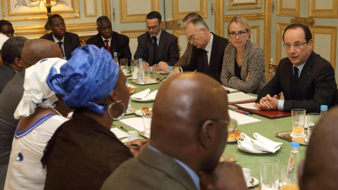 French President Francois Hollande, right, speaks with members of Malian associations in France during a meeting at the Elysee Palace in Paris, Sunday, Jan. 13, 2013. Niger, Burkina Faso, Senegal and Nigeria agreed on Saturday to send soldiers, a day after France authorized air strikes, dispatching fighter jets from neighboring Chad and bombing rebel positions north of Mopti, the last Malian-controlled town. (AP Photo/Philippe Wojazer, Pool)