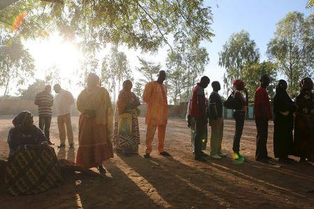 People queue to vote during the presidential and legislative election at a polling station in Ouagadougou