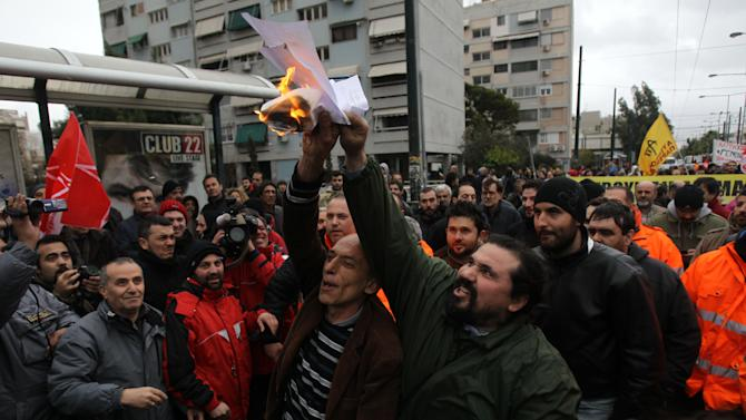 Metro workers burn civil mobilization's documents outside Aghios Antonios station in western Athens on Friday, Jan. 25, 2013. Striking Athens metro workers returned to the job Friday, hours after the Greek government used riot police to evacuate holdouts from a subway depot, ending a bitter standoff over new austerity measures. The nine-day strike _ which knocked out a system serving more than  a million people a day _ was the biggest labor unrest Greece's uneasy,  conservative-led governing coalition faced since taking over last June. (AP Photo/Thanassis Stavrakis)