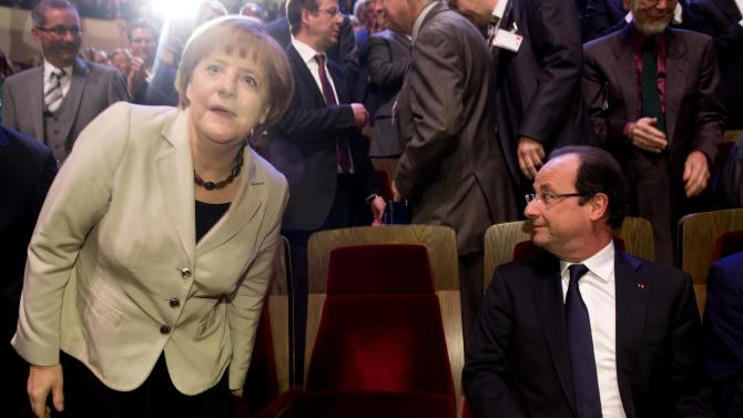 French President Francois Hollande , right, and German Chancellor Angela Merkel, left, get seated at the Gewandhaus concert hall in Leipzig, eastern Germany, as they arrive to attend festivities to mark the German Social Democratic SPD party's 150th anniversary on Thursday  May 23, 2013. The SPD, Europe's oldest political party, has invited nearly 50 current and former heads of state and government as it celebrates 150th birthday and its turbulent history, which saw it advance workers rights and suffer persecution by the Nazis. The SPD was founded on May 23, 1863 in Leipzig as the 'Allgemeiner Deutscher Arbeiterverein' (common German worker's club).  (AP Photo/Odd Andersen, Pool)