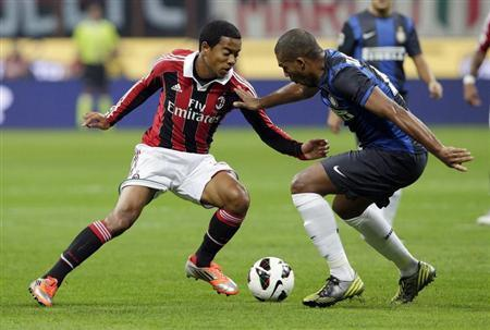 Inter Milan's Juan Jesus challenges AC Milan's Urby Emanuelson during their Italian Serie A soccer match in Milan