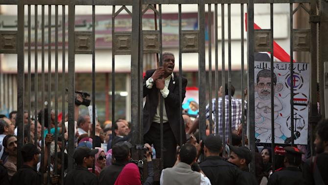 "An Egyptian man chants slogans and one holds a cartoon of Egypt's president, Mohammed Morsi, with Arabic writing that reads, ""the match still on the - field"", during a protest in front of the judges club in downtown Cairo, Egypt, Wednesday, April 24, 2013.  Egypt's Islamist-led parliament on Wednesday pushed ahead with a controversial judicial law in a heated session, despite a rising uproar among judges and the opposition who fear Islamists' control over courts. (AP Photo/Khalil Hamra)"